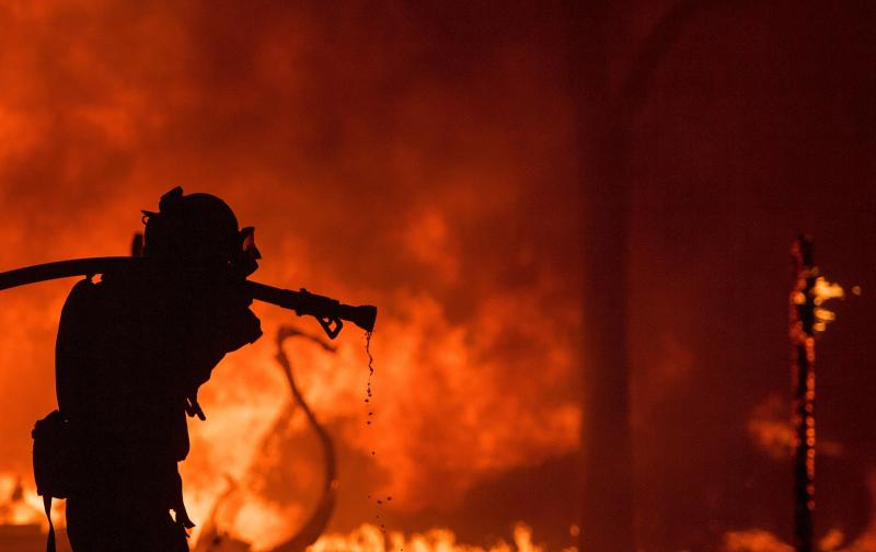 A firefighter pulls a hose in front of a burning house in the Napa wine region of California on Oct. 9, 2017. (JOSH EDELSON/AFP/Getty Images)