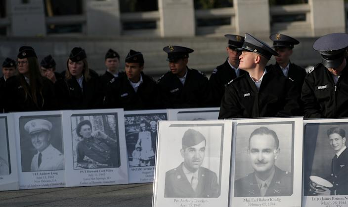 """Cadets hold portraits of loved ones who died during World War II at a Veterans Day Observance to honor """"the 16 million men and women who served in World War II"""" in Washington, Nov. 11, 2019. (Photo: Siphiwe Sibeko/Reuters)"""