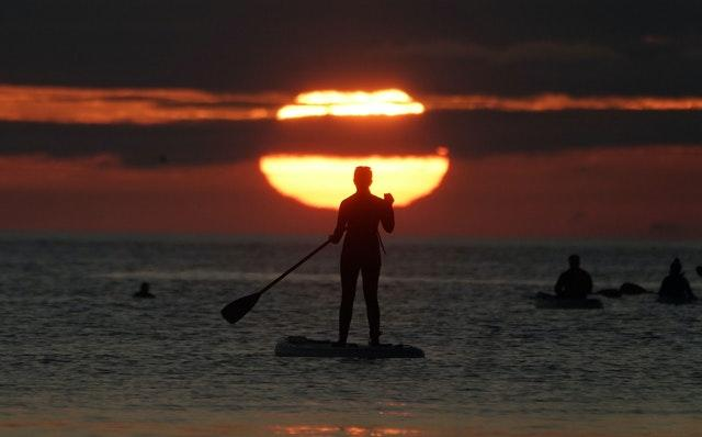 A paddleboarder watches the sunrise at Cullercoats bay in North Tyneside