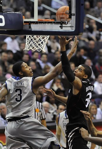 Cincinnati's Dion Dixon, right, goes up for a shot against Georgetown's Mikael Hopkins during first half of an NCAA college basketball game, Monday, Jan. 9, 2012, in Washington. (AP Photo/Richard Lipski)