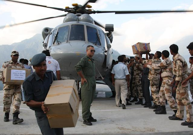 "In this photograph received from the Ministry of Defence on June 20, 2013, Indian military personnel unload relief supplies from an Indian Air Force Mi-17 helicopter following flash floods in the northern Uttarakhand state. India's military battled on June 20 to reach villages and towns cut off by flash floods and landslides in the country's north as officials warned at least 1,000 people may have been killed. AFP PHOTO/INDIAN ARMY ----EDITORS NOTE---- RESTRICTED TO EDITORIAL USE - MANDATORY CREDIT - ""AFP PHOTO/INDIAN ARMY"" - NO MARKETING NO ADVERTISING CAMPAIGNS - DISTRIBUTED AS A SERVICE TO CLIENTS -----"