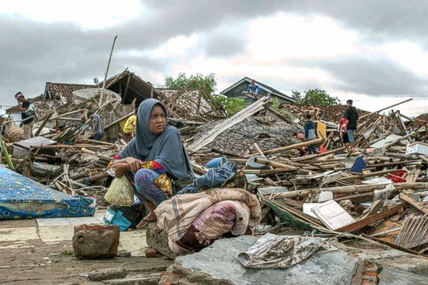 PHOTO: A tsunami survivor sits on a piece of debris as she salvages items from the location of her house in Sumur, Indonesia, Dec. 24, 2018. (Fauzy Chaniago/AP)