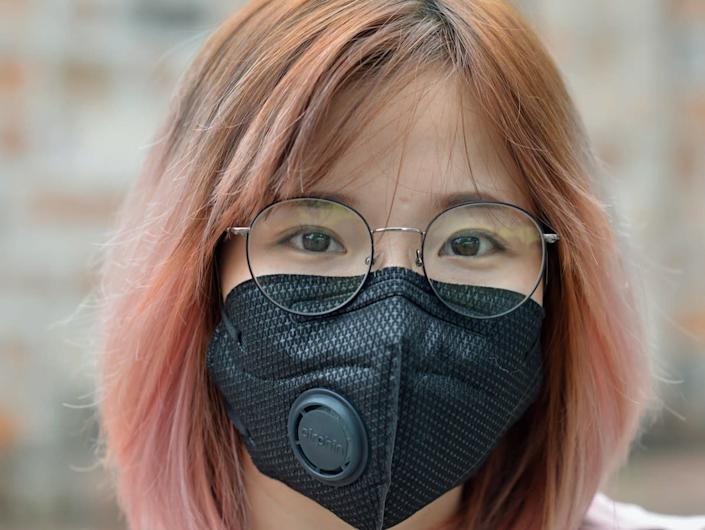 woman with dyed hair and eyeglasses wears a black protective face mask with breathing valve.