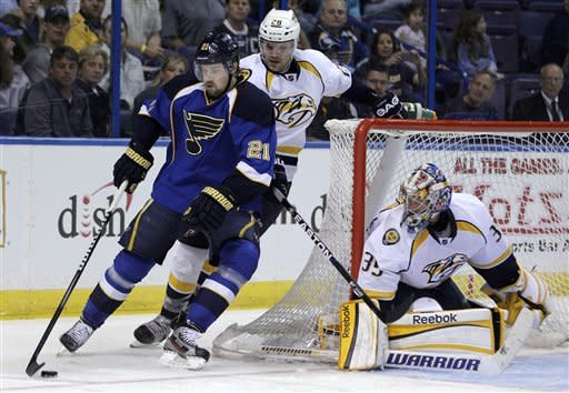 St. Louis Blues' Patrik Berglund, of Sweden, handles the puck as Nashville Predators' Paul Gaustad, center, and goalie Pekka Rinne, of Finland, defend during the second period of an NHL hockey game Tuesday, March 27, 2012, in St Louis. (AP Photo/Jeff Roberson)
