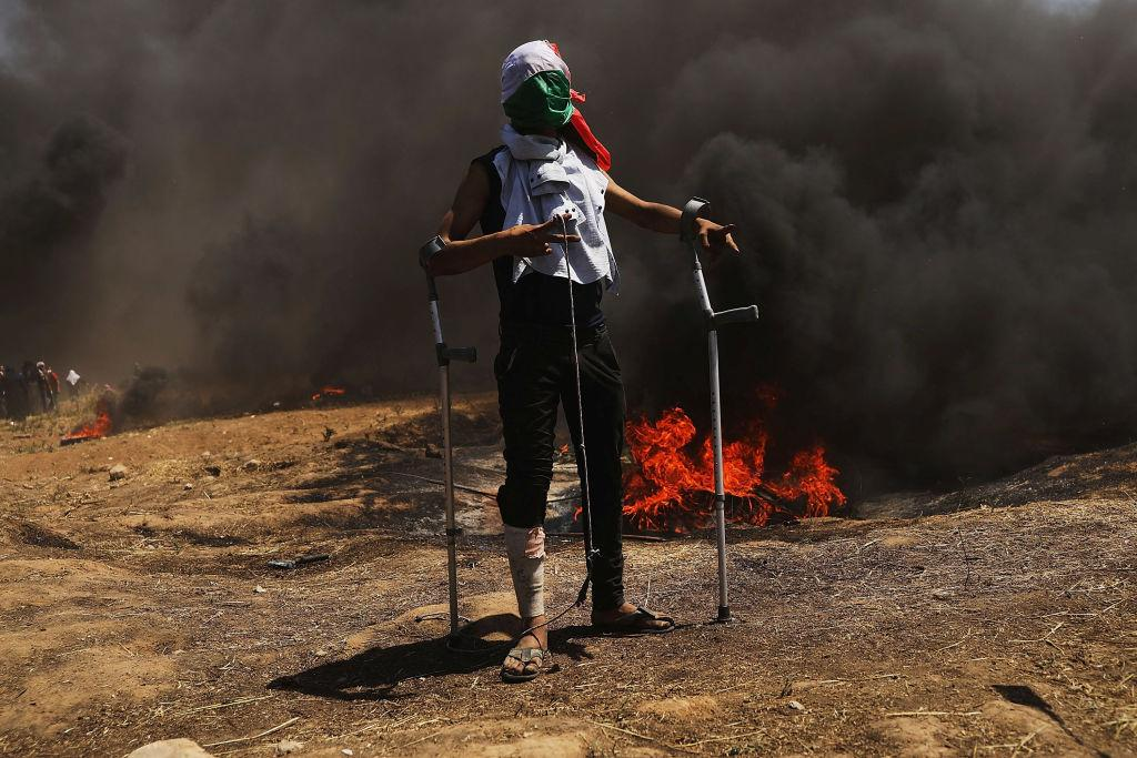 <p>A Palestinian man pauses as clashes with Israeli soldiers at the border fence with Israel continue during mass demonstrations at the fence on May 14, 2018 in Gaza City, Gaza. Israeli soldiers killed at least 41 Palestinians and wounded over a thousand as the demonstrations coincided with the controversial opening of the U.S. Embassy in Jerusalem. This marks the deadliest day of violence in Gaza since 2014. Gaza's Hamas rulers have vowed that the marches will continue until the decade-old Israeli blockade of the territory is lifted. (Photo from Spencer Platt/Getty Images) </p>