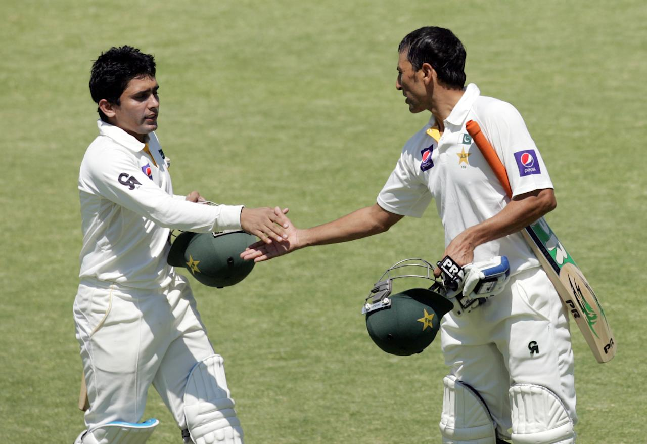 Pakistan's batsmen Adnan Akmal (L) and Younis Khan (R) shake hands before walking from the pitch at tea break during the fourth day of the first cricket test match between Pakistan and hosts Zimbabwe at the Harare Sports Club September 6, 2013. AFP PHOTO / JEKESAI NJIKIZANA        (Photo credit should read JEKESAI NJIKIZANA/AFP/Getty Images)