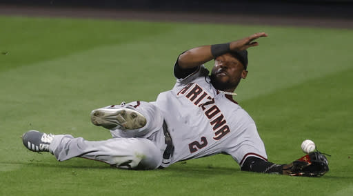 Arizona Diamondbacks center fielder Starling Marte tries to catch a ball hit by Colorado Rockies' Raimel Tapia that fell in for a two-run double during the eighth inning of a baseball game Tuesday, Aug. 11, 2020, in Denver. The Rockies won 8-7. (AP Photo/David Zalubowski)