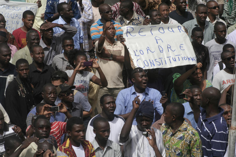 People gather in protest against the recent military coup, in Bamako, Mali, Monday, March 26, 2012, with one protester holding a sign reading 'Return to constitutional order'.  About a thousand demonstrators protested Monday in Mali's capital to demand a return to constitutional order days after mutinous soldiers claimed power in a coup.(AP Photo/Harouna Traore)