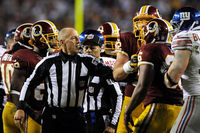 LANDOVER, MD - DECEMBER 03: Referee Terry McAulay #77 holds back a Washington Redskins player in the third quarter after a Alfred Morris #46 of the Washington Redskins fumble against the New York Giants at FedExField on December 3, 2012 in Landover, Maryland. (Photo by Patrick McDermott/Getty Images)
