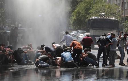 Turkish police use a water cannon to disperse demonstrators during a protest against the replacement of Kurdish mayors with state officials in three cities, in Diyarbakir