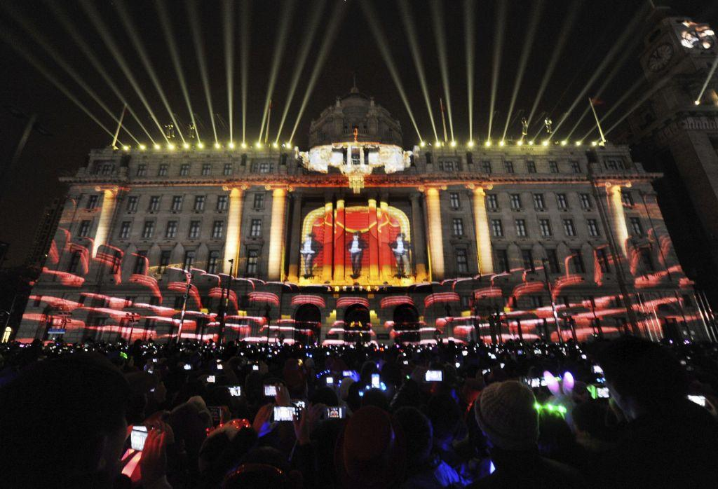 Visitors take pictures and videos during a light show as part of a New Year countdown celebration at the financial square on the Bund in Shanghai December 31, 2012. Picture taken December 31, 2012.