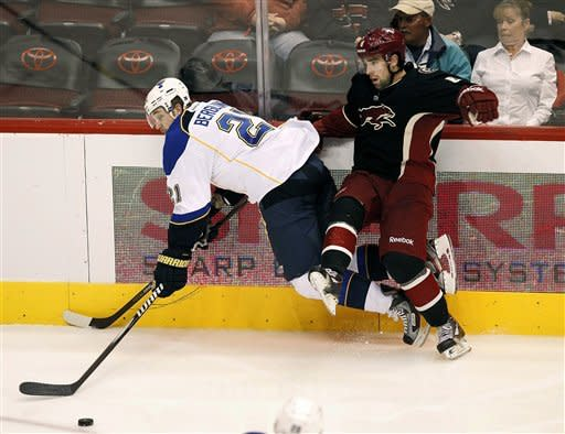 St. Louis Blues' Patrik Berglund (21) and Phoenix Coyotes' David Schlemko battle for the puck during the second period of an NHL hockey game, Friday, Dec. 23, 2011, in Glendale, Ariz. (AP Photo/Matt York)