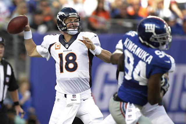 Denver Broncos quarterback Peyton Manning (18) throws a pass during the first half of an NFL football game as New York Giants linebacker Mathias Kiwanuka (94) rushes the passer Sunday, Sept. 15, 2013, in East Rutherford, N.J. (AP Photo/Kathy Willens)