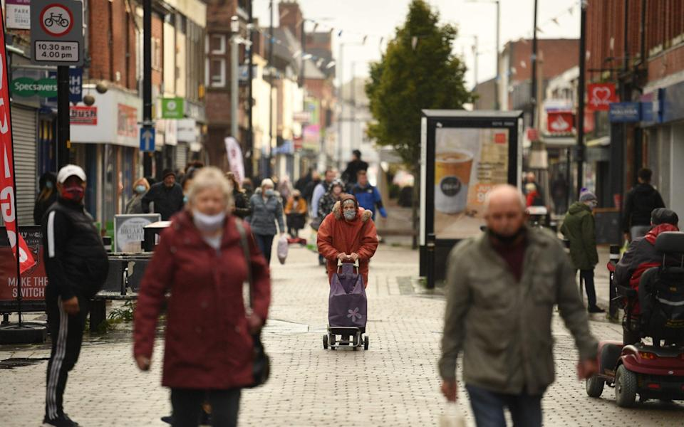 People wearing masks because the novel coronavirus pandemic walk in the high street in Leigh, Greater Manchester - Oli Scarff/AFP