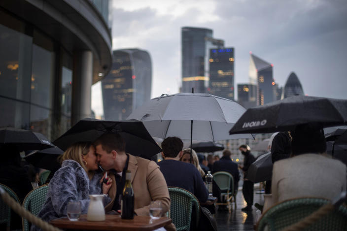 People endure the wet and windy Bank Holiday weekend weather to sit outside a restaurant near Tower Bridge in central London on Monday, May 3, 2021. (Victoria Jones/PA via AP)