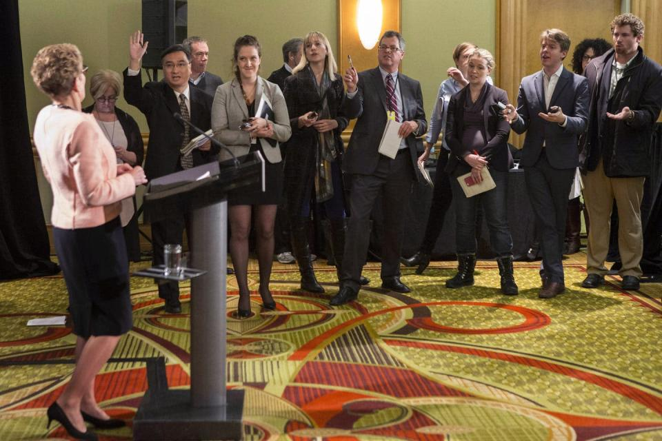Reporters are lined up to ask questions of a politician standing at a lecturn