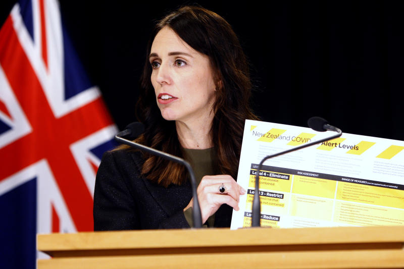 FILE - In this March 21, 2020, file photo, New Zealand Prime Minister Jacinda Ardern holds up a card showing a new alert system for COVID-19 in Wellington, New Zealand. New Zealand has set itself an ambitious goal of not just containing the coronavirus, but eliminating it altogether. Experts believe the country could pull it off, thanks to its geography and decisive early actions by Ardern, who has put the country into a strict lockdown. But whatever happens, the country will continue feeling the effects of the pandemic, which has hobbled its vital tourism industry. (AP Photo/Nick Perry, File)
