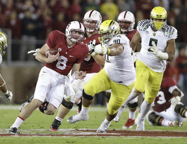 Stanford quarterback Kevin Hogan (8) runs from Oregon defensive tackle Ricky Havili-Heimuli (90) during the second quarter of an NCAA college football game in Stanford, Calif., Thursday, Nov. 7, 2013. (AP Photo/Marcio Jose Sanchez)