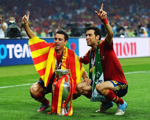 KIEV, UKRAINE - JULY 01: Xavi Hernandez (L) and Sergio Busquets of Spain pose with the trophy following victory in the UEFA EURO 2012 final match between Spain and Italy at the Olympic Stadium on July 1, 2012 in Kiev, Ukraine. (Photo by Laurence Griffiths/Getty Images)