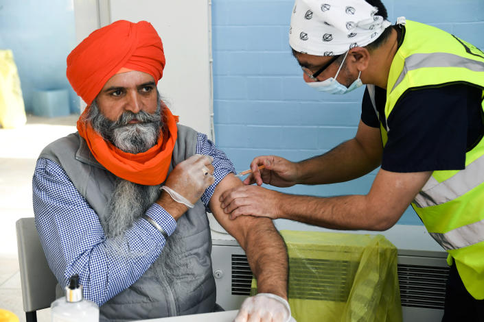 Dr Manraj Barhey administers a dose of AstraZeneca COVID-19 vaccine to Baltjit Singh, at the Guru Nanak Gurdwara Sikh temple, on the day the first Vaisakhi Vaccine Clinic is launched, in Luton, England, Sunday, March 21, 2021. (AP Photo/Alberto Pezzali)