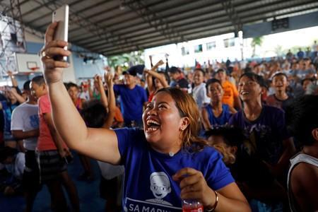 Filipino boxing fans celebrate after Manny Pacquiao wins the WBA Welterweight match against Keith Thurman of the U.S. during a live public viewing of the match in Marikina