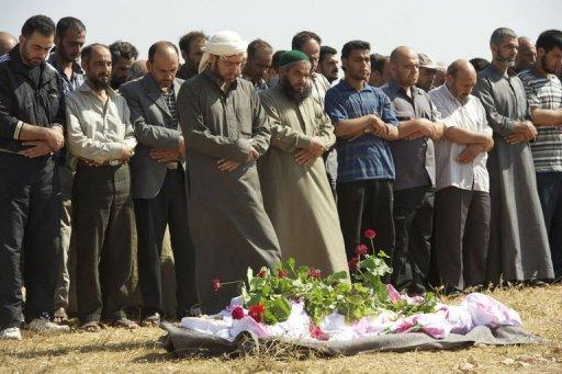 Syrian mourners pray over the body of a member of the Free Syrian Army in Homs
