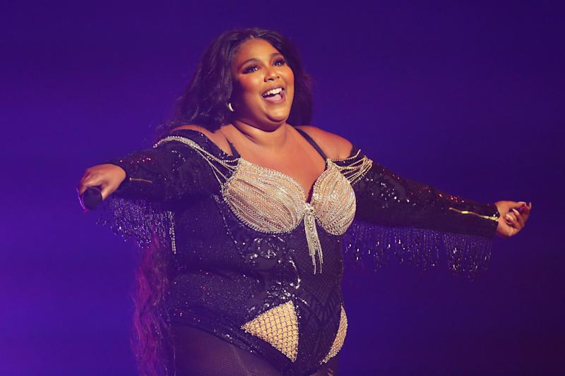 Lizzo poses on stage with her arms out stretched