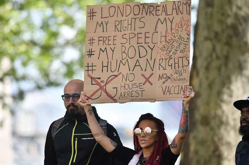 A protestor holds a placard outside New Scotland Yard