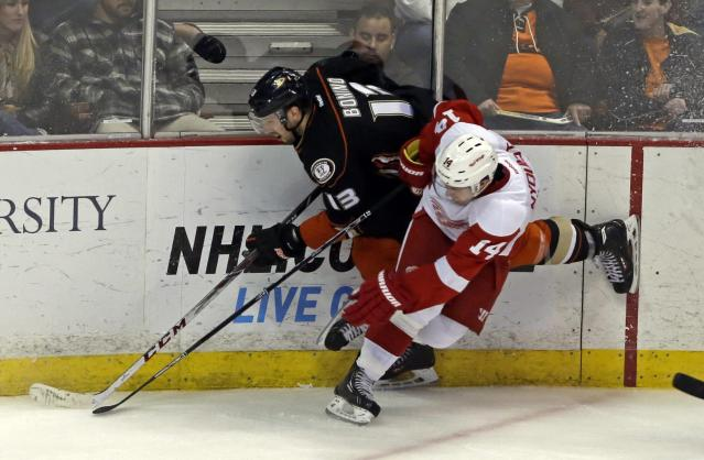 Anaheim Ducks center Nick Bonino (13) and Detroit Red Wings right winger Gustav Nyquist (14), of Sweden, get tangled up in the second period of an NHL hockey game in Anaheim, Calif., Sunday, Jan. 12, 2014. (AP Photo/Reed Saxon)