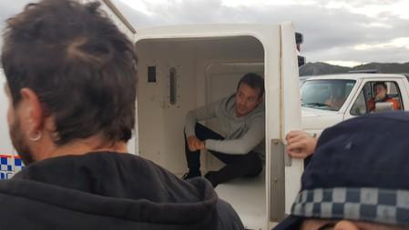 French TV reporter Hugo Clement is seen in a police van after he was arrested while filming protesters blockading the Abbot Point coal port near Bowen