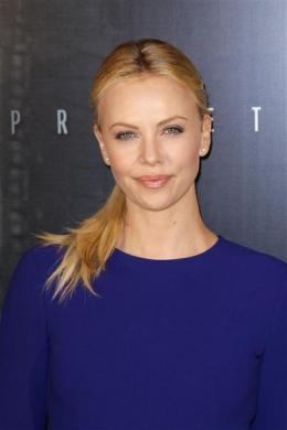 """Charlize Theron poses as she arrives at the French premiere of the movie """"Prometheus"""" in Paris, April 11, 2012."""