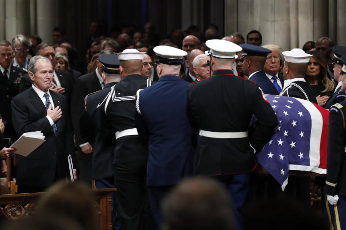 Former President George W. Bush places his hand over his heart as the flag-draped casket of former President George H.W. Bush is carried by a joint services military honor guard after the State Funeral at the National Cathedral, Wednesday, Dec. 5, 2018, in Washington. (Photo: Alex Brandon, Pool/AP)