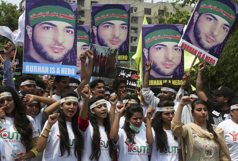 Members of the non-governmental organization 'Youth Forum for Kashmir' hold posters of a young rebel leader Burhan Wani, who was killed by Indian troops last year, while chanting anti Indian slogans during a rally to mark the 1st anniversary of his death, in Lahore, Pakistan, Saturday, July 8, 2017. (AP Photo/K.M. Chaudary)