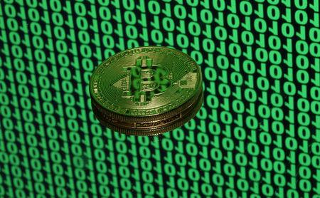 Bitcoin token is seen placed on a monitor that displays binary digits in this illustration picture