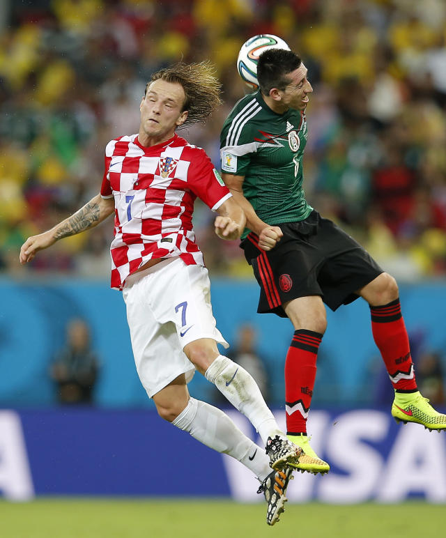 Croatia's Ivan Rakitic, left, and Mexico's Hector Herrera go for a header during the group A World Cup soccer match between Croatia and Mexico at the Arena Pernambuco in Recife, Brazil, Monday, June 23, 2014. (AP Photo/Eduardo Verdugo)