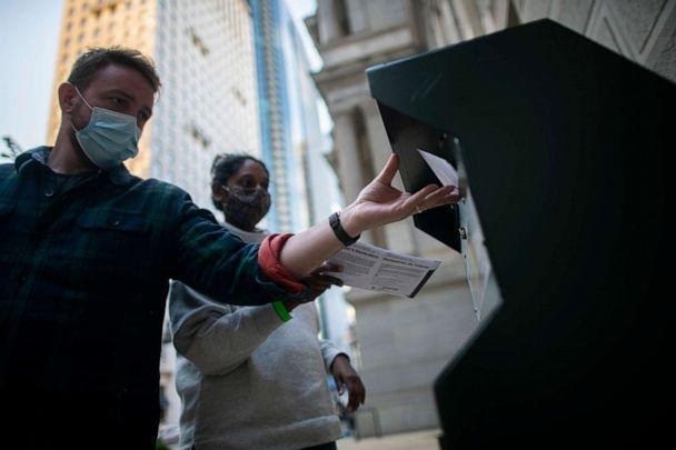 PHOTO: Voters cast their early voting ballot at a drop box outside of City Hall on Oct. 17, 2020 in Philadelphia. (Mark Makela/Getty Images)