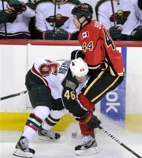 Minnesota Wild's' Jared Spurgeon, left, runs into Calgary Flames' Chris Butler during third period NHL action in Calgary, Alberta, Tuesday Dec. 20, 2011. (AP Photo/The Canadian Press, Larry MacDougal)