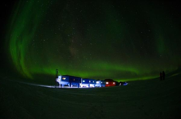 The Halley VI Research Station at night, with the Southern Lights visible in the sky.