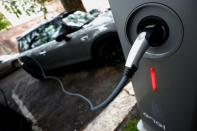 FILE PHOTO: An electric car is plugged in at a charging point for electric vehicles in Rome