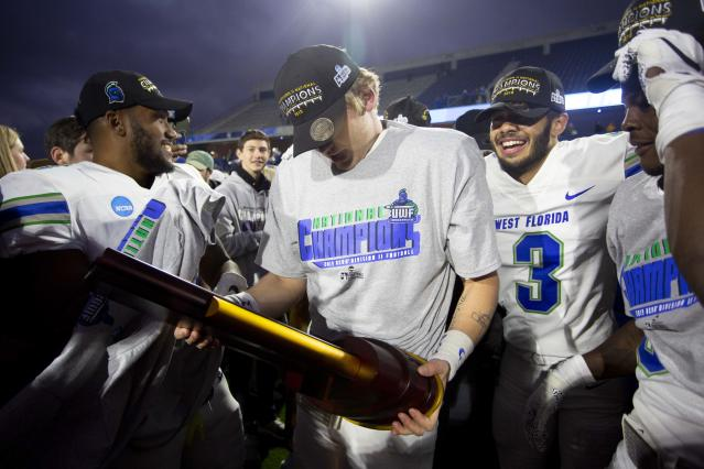 West Florida quarterback Austin Reed, center, holds the trophy while celebrating with teammates after the team won the Division II championship NCAA college football game against Minnesota State, Saturday, Dec. 21, 2019, in McKinney, Texas. (AP Photo/Gareth Patterson)