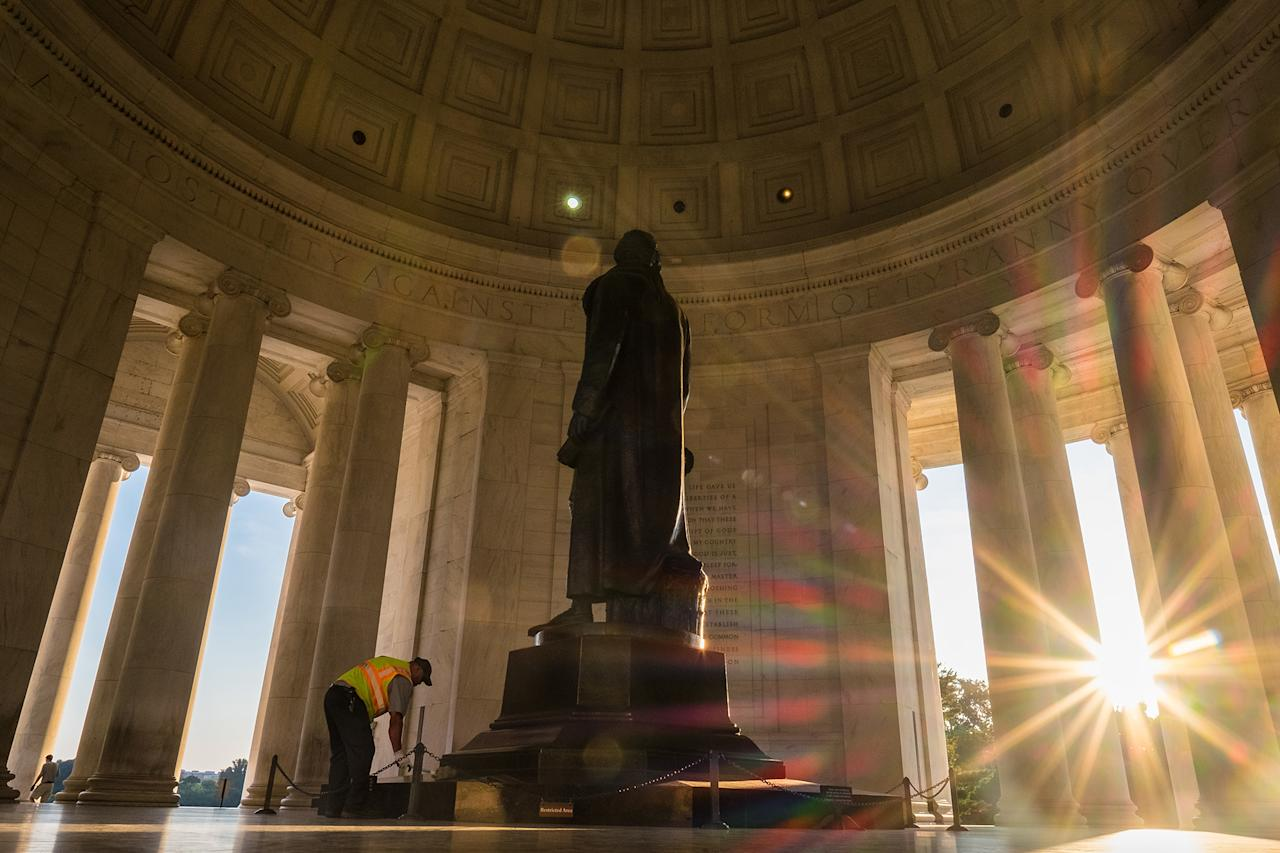 <p>A U.S. Park Service employee dusts off the statute of Thomas Jefferson as the sun streaks through the pillars at the Jefferson Memorial in Washington, early in the morning, July 8, 2016. The temperature is expected to reach the 90s in the Nation's Capital today. (Photo: J. David Ake/AP) </p>