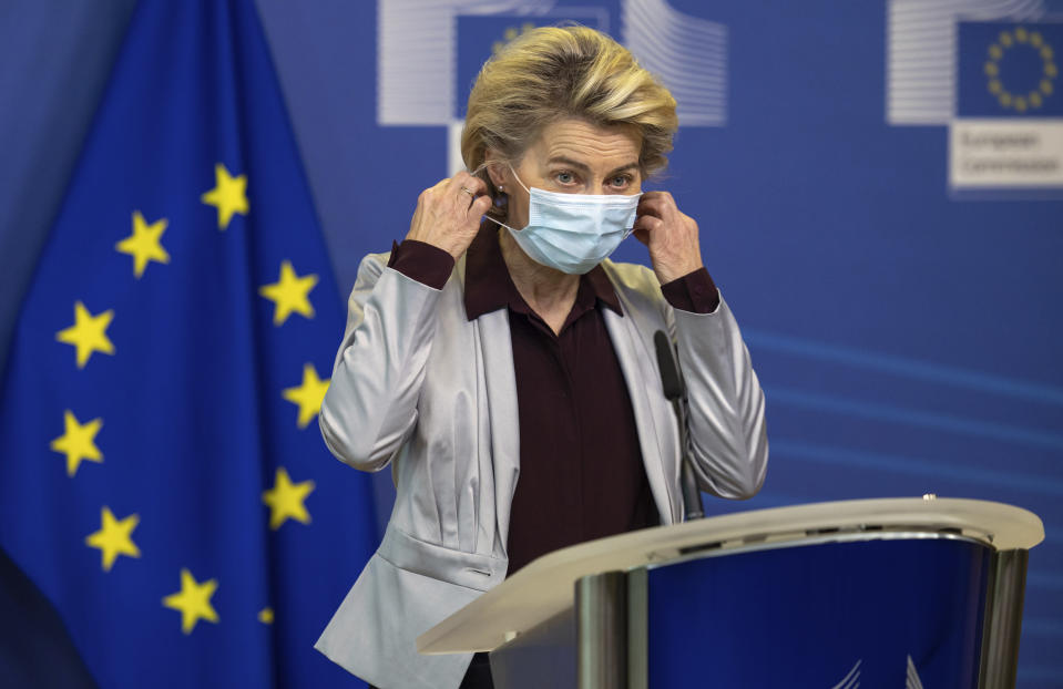 European Commission President Ursula von der Leyen takes off her protective face mask as she prepares to deliver a statement at EU headquarters in Brussels, Tuesday, Nov. 24, 2020. The European Commission announced on Tuesday that it has approved a new contract to secure another COVID-19 vaccine for Europeans. (AP Photo/Olivier Matthys, Pool)