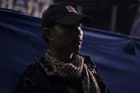 A guard from the anti-government protesters guards the stage as protest leader Suthep Thaugsuban speaks to his supporters during a rally in central Bangkok