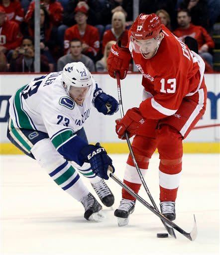 Vancouver Canucks defenseman Alexander Edler (23), of Sweden, tries to block a shot by Detroit Red Wings center Pavel Datsyuk (13), of Russia, in the second period of an NHL hockey game Sunday, Feb. 24, 2013, in Detroit. (AP Photo/Duane Burleson)