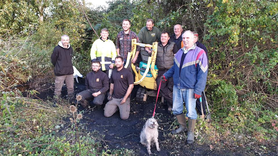 The rescue team with Bella the dog after she was freed (Picture: SWNS)