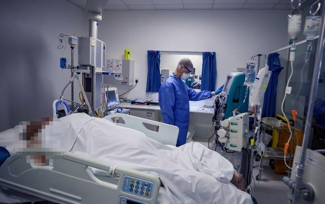 A health worker tends to a patient on an ICU