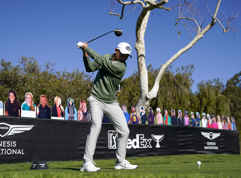 Collin Morikawa tees off on the 18th hole in front of cardboard cutout fans during the Genesis Invitational pro-am golf event at Riviera Country Club, Wednesday, Feb. 17, 2021, in the Pacific Palisades area of Los Angeles. (AP Photo/Ryan Kang)