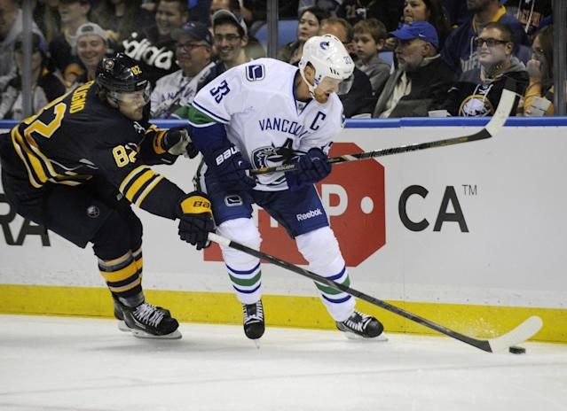 Buffalo Sabres left winger Marcus Foligno (82) knocks the puck away from Vancouver Canucks center Henrik Sedin (33), of Sweden, during the first period of an NHL hockey game in Buffalo, N.Y., Thursday, Oct. 17, 2013. (AP Photo/Gary Wiepert)
