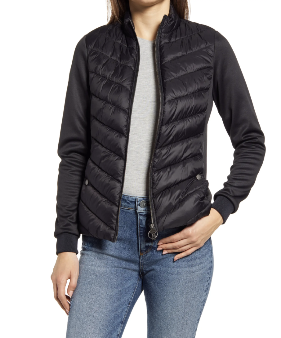 model wearing black quilted barbour jacket, grey t-shirt, and jeans
