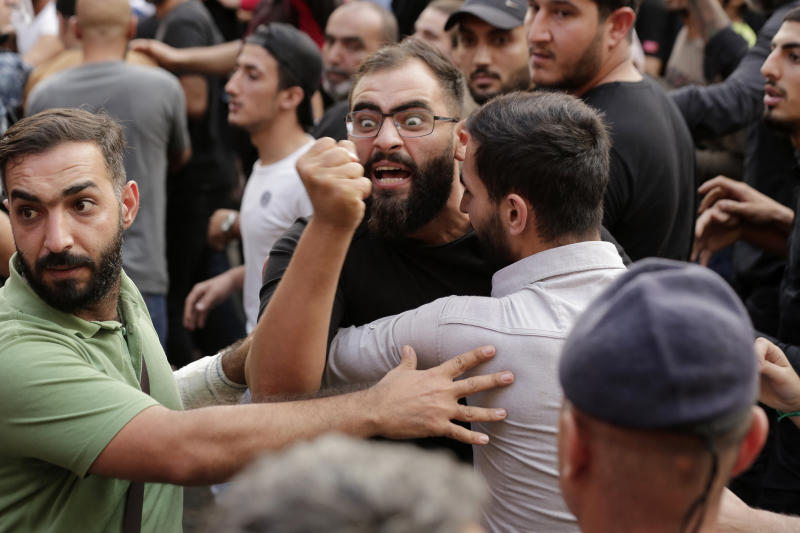 FILE - In this Oct. 25, 2019 file photo, anti-government protesters and Hezbollah supporters clash during a protest in Beirut, Lebanon.  Lebanon's protests have shown unusual overt anger at the country's powerhouse, Hezbollah. (AP Photo/Hassan Ammar, File)
